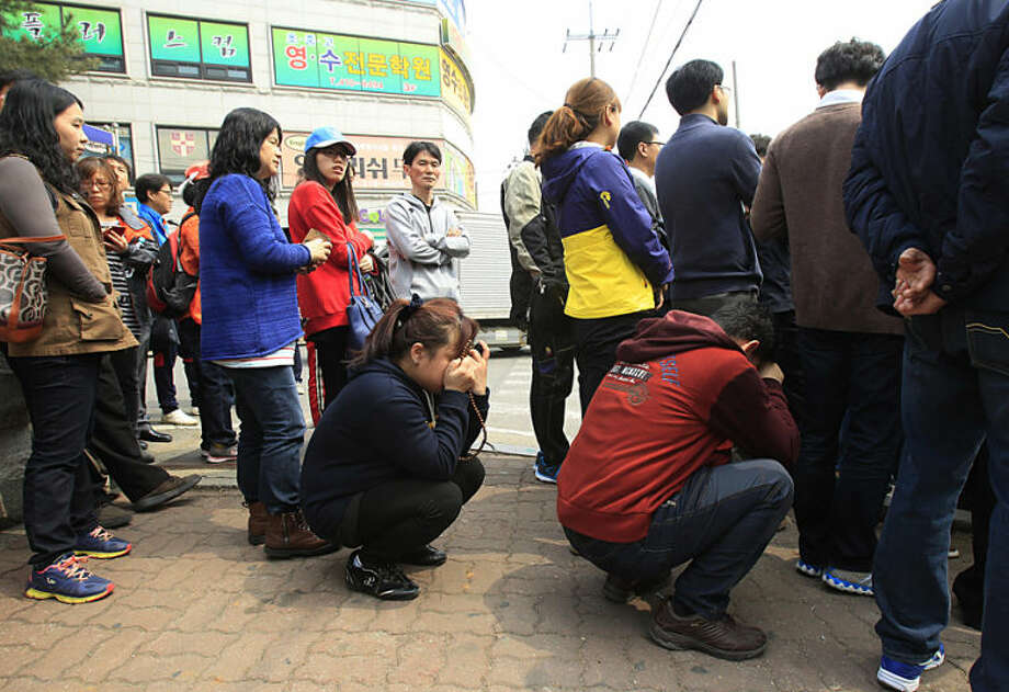 Parents wait for a bus to meet with their children rescued from a ferry that sank off the country's southern coast, at Danwon high school in Ansan, South Korea, Wednesday, April 16, 2014. Dozens of boats, helicopters and divers scrambled to rescue more than 470 people, including 325 students on a school trip from the high school, after the ferry sank earlier in the day. (AP Photo/Ahn Young-joon)