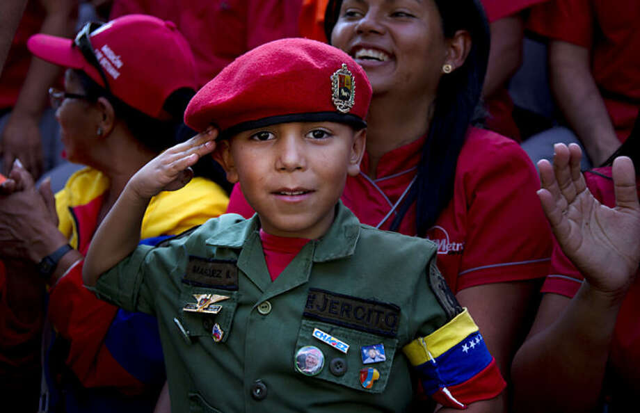 A boy dressed in a military costume salutes toward the camera during an event marking President Nicolas Maduro's first year in office in Caracas, Venezuela, Tuesday, April 15, 2014. Maduro took over leadership of Hugo Chavez's political movement following the leader's death from cancer and went on to win elections soon after in April 2013. (AP Photo/Ramon Espinosa)