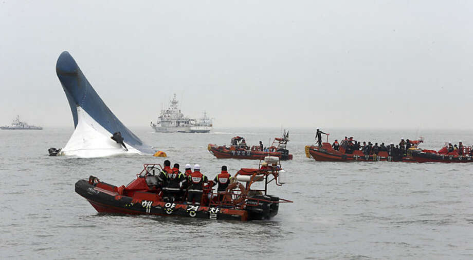 South Korean coast guard officers try to rescue passengers from ferry Sewol in the water off the southern coast near Jindo, south of Seoul, South Korea, Wednesday, April 16, 2014. Dozens of boats, helicopters and divers scrambled Wednesday to rescue more than 470 people, including 325 high school students on a school trip, after the ferry sank off South Korea's southern coast. (AP Photo/Hyung Min-woo, Yonhap) KOREA OUT
