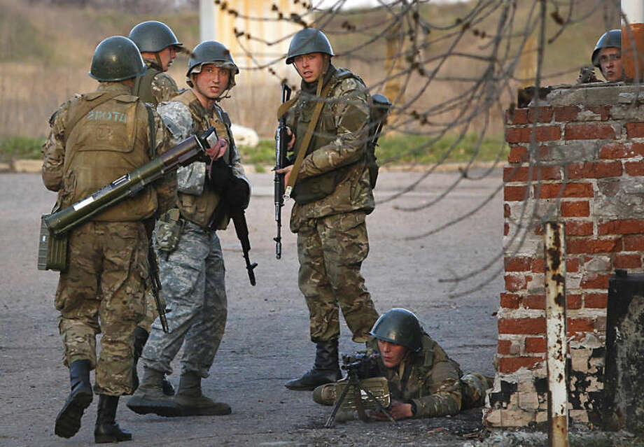 Ukrainian army troops set up a position at an airport in Kramatorsk, eastern Ukraine, Tuesday, April 15, 2014. In the first Ukrainian military action against a pro-Russian uprising in the east, government forces clashed Tuesday with about 30 armed gunmen at a small airport in Kramatorsk. (AP Photo/Sergei Grits)