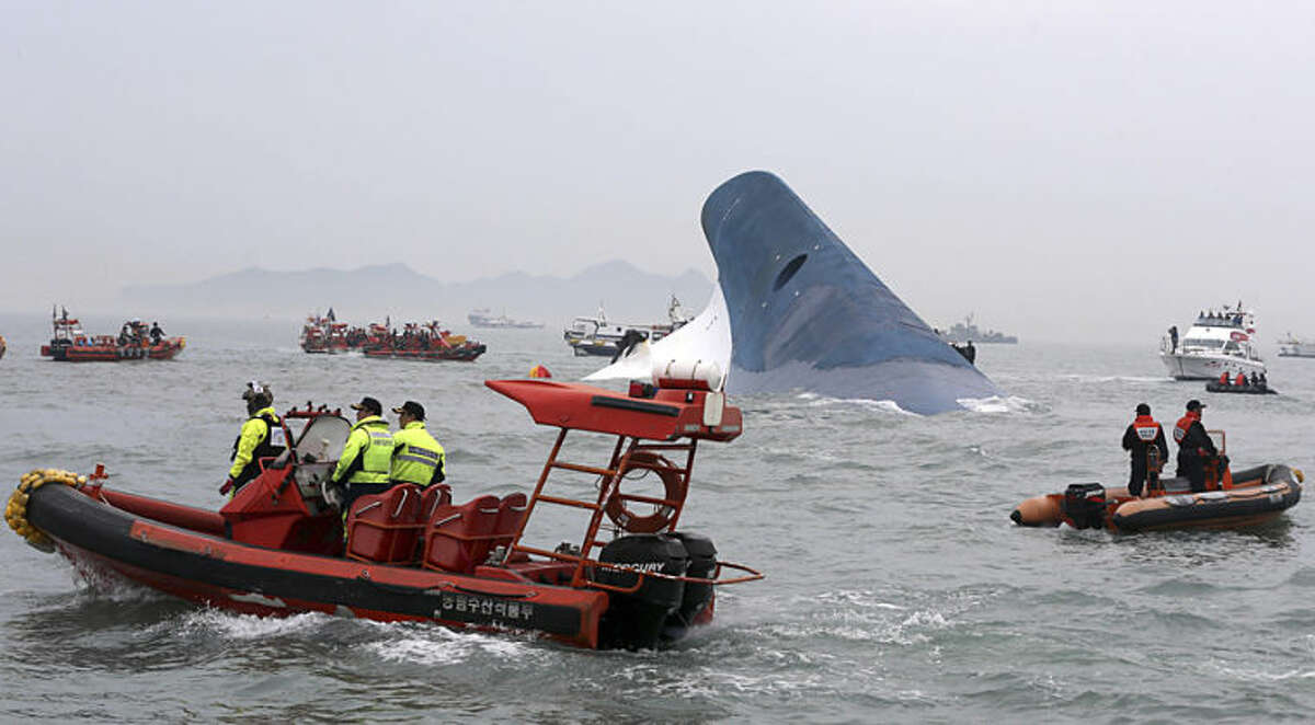 South Korean coast guard officers and rescue team members try to rescue passengers from the ferry Sewol in the water off the southern coast near Jindo, south of Seoul, Wednesday, April 16, 2014. Dozens of boats, helicopters and divers scrambled Wednesday to rescue more than 470 people, including 325 high school students on a school trip, after a ferry sank off South Korea's southern coast. (AP Photo/Yonhap, Hyung Min-woo) KOREA OUT