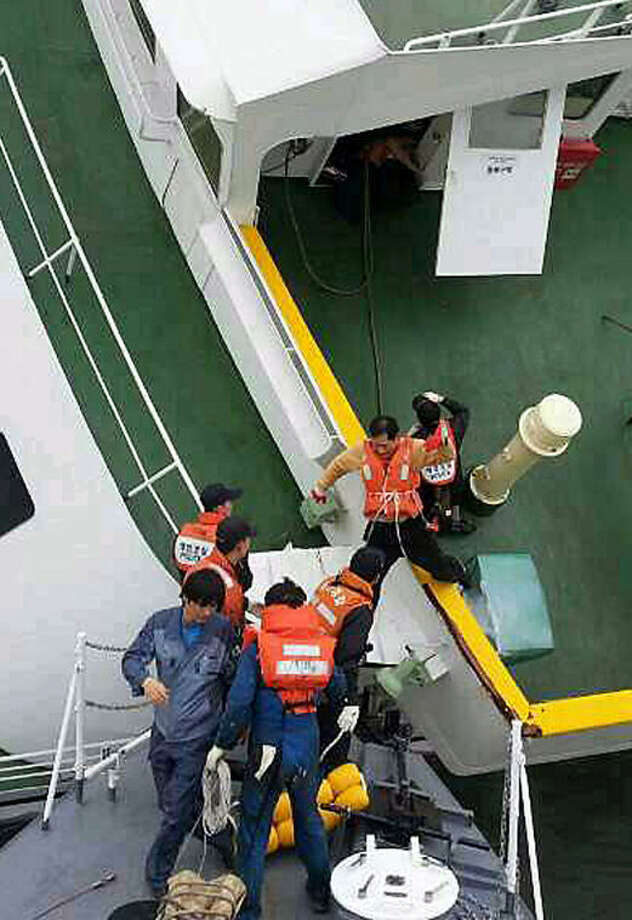 In this photo released by South Korea Coast Guard via Yonhap News Agency, South Korean coast guard rescue passengers from a ferry in the water off the southern coast near Jindo, South Korea, Wednesday, April 16, 2014. The ferry carrying 459 people, mostly high school students on an overnight trip to a tourist island, sank off South Korea's southern coast on Wednesday, leaving nearly 300 people missing despite a frantic, hours-long rescue by dozens of ships and helicopters. (AP Photo/South Korea Coast Guard via Yonhap) KOREA OUT