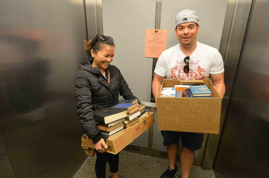 Carla and Joe Lopez ride the elevator up with boxes of just bought history books at the weekends Wilton Library Annual Gigantic Book Sale in Wilton Center April 24 2016