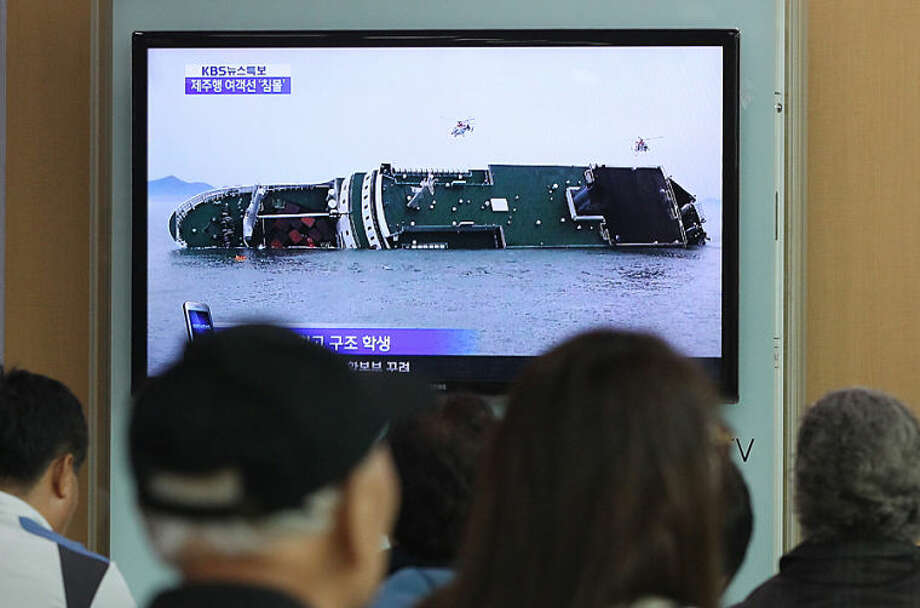 People watch a TV news program showing a sinking passenger ship, at Seoul Railway Station in Seoul, South Korea, Wednesday, April 16, 2014. The South Korean passenger ship carrying more than 470 people, including many high school students, is sinking off the country's southern coast Wednesday after sending a distress call, officials said. There are no immediate reports of causalities.(AP Photo/Ahn Young-joon)