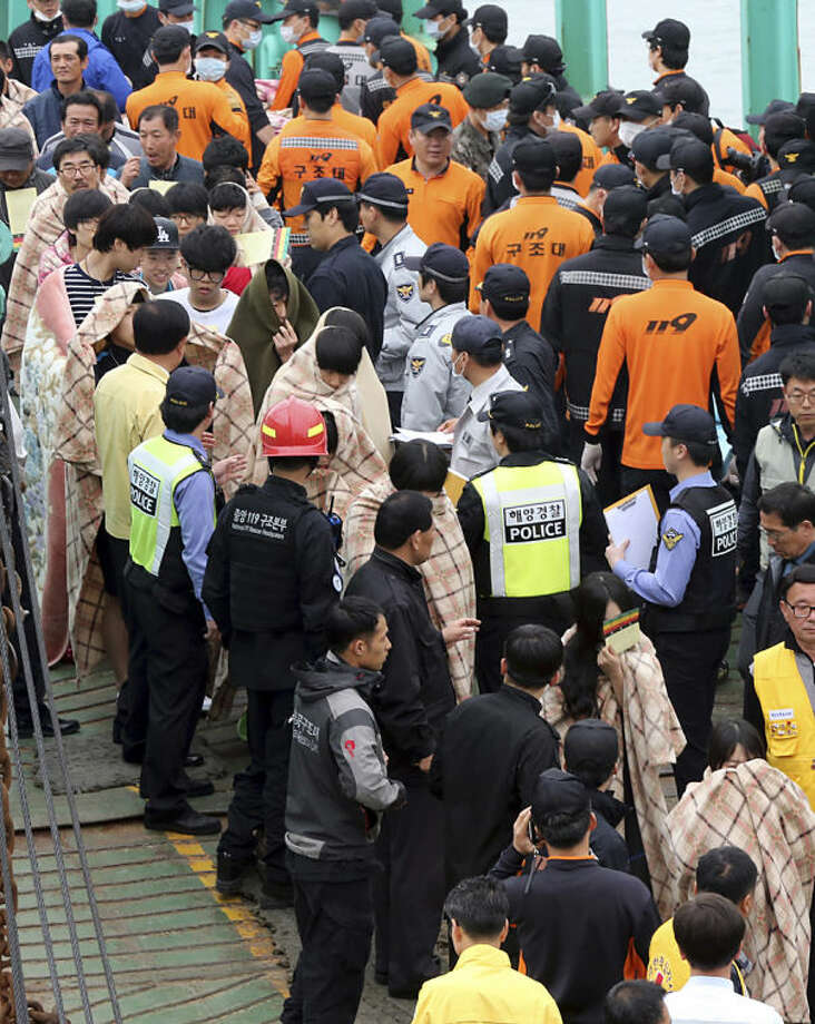 Rescued passengers from a ferry sinking off South Korea's southern coast, are escorted by rescue teams on their arrival at a port in Jindo, south of Seoul, South Korea, Wednesday, April 16, 2014. More than 100 people were still unaccounted Wednesday several hours after the ferry carrying 476, most of them high school students, sank in cold waters off South Korea's southern coast. (AP Photo/Yonhap, Park Chul-heung) KOREA OUT