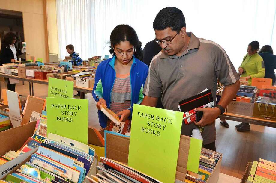 Samhita and father Raju Kakarlapudi shop for a book for a family member during the Wilton Library Gigantic Book Sale on Sunday