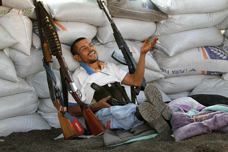 """FILE- In this Feb. 9, 2014, file photo, flanked by weapons a man from a self-defense group sits inside a barricade at the entrance of Apatzingan in Michoacan state, Mexico. Vigilantes who have driven a quasi-religious drug cartel from a series of towns in western Mexico entered Apatzingan on Saturday and were working with government forces to clear it of cartel gunmen. The Mexican government announced Tuesday April 15, 2014, that vigilante groups in the western state of Michoacan will have until May 10 to register their guns and decide whether to join the army's """"rural defense corps."""" (AP Photo/Marco Ugarte File)"""