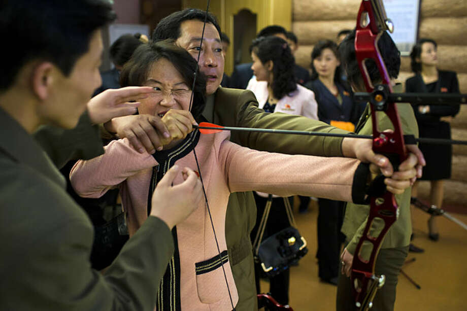 A North Korean man helps a woman fire a bow and arrow at a firing range at the Meari Shooting Gallery in Pyongyang on Wednesday, April 16, 2014. (AP Photo/David Guttenfelder)