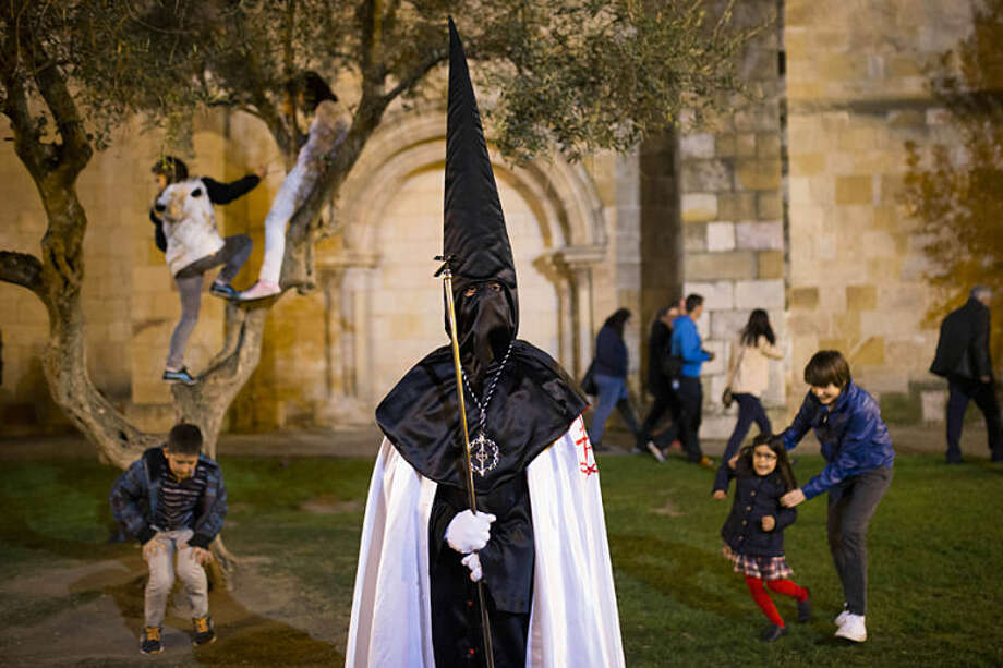 """Children play in the background as a penitent watches a march from """"Jesus en su Tercera Caída"""" brotherhood during a procession in Zamora, Spain, Monday, April 14, 2014. Hundreds of processions take place throughout Spain during the Easter Holy Week. (AP Photo/Andres Kudacki)"""