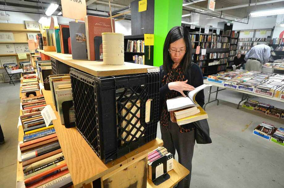Starlet Wu reads a few pages of a poetry book during the Wilton Library Annual Gigantic Book Sale on Sunday in Wilton Conn. April 24 2016