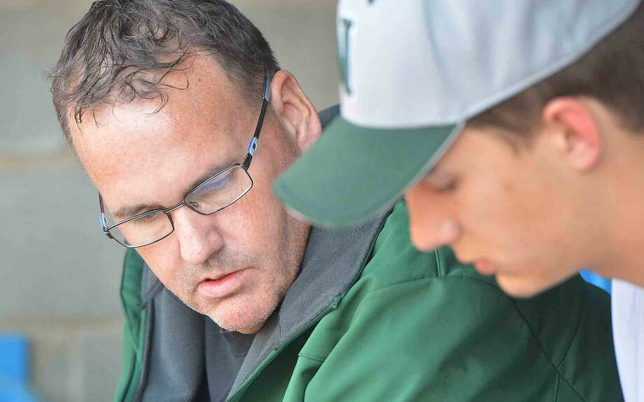 Steve Brueski works with the players in the Norwalk High School baseball team dugout during a game on April 21 2016