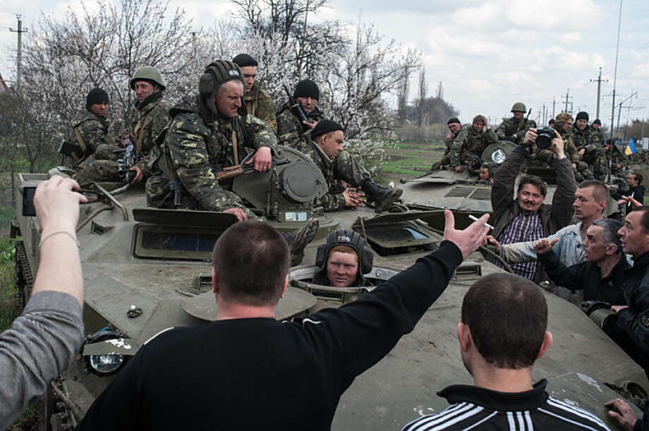 People block a column of Ukrainian Army combat vehicles on their way to the town of Kramatorsk on Wednesday, April 16, 2014. The central government has so far been unable to rein in the insurgents, who it says are being stirred up by paid operatives from Russia and have seized numerous government facilities in at least nine eastern cities to press their demands for broader autonomy and closer ties with Russia. (AP Photo/ Evgeniy Maloletka)