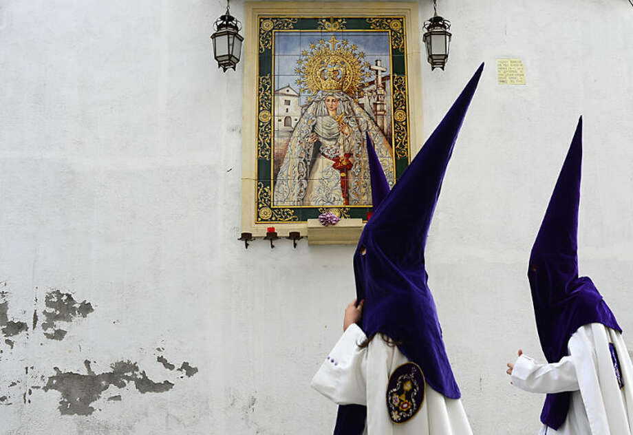 """Penitents from """"La Sangre"""" brotherhood walk to the church prior to the Holy Week procession in Cordoba, southern Spain, Spain, Tuesday, April 15, 2014. Hundreds of processions take place throughout Spain during the Easter Holy Week(AP Photo/Manu Fernandez)"""