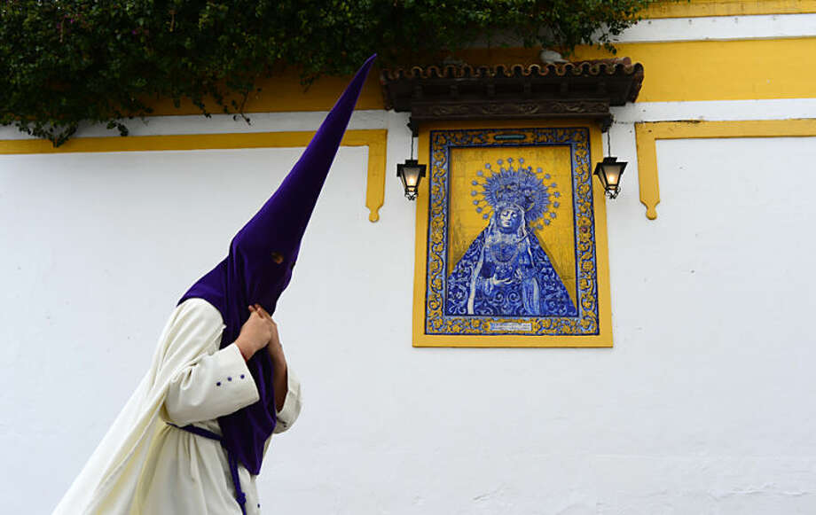 """A penitent from """"La Sangre"""" brotherhood walks to the church prior of a Holy Week procession in Cordoba, southern Spain, Spain, Tuesday, April 15, 2014. Hundreds of processions take place throughout Spain during the Easter Holy Week(AP Photo/Manu Fernandez)"""