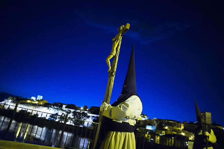 """Penitents from """"Jesus del Via Crucis"""" brotherhood cross a bridge as they take part in a procession in Zamora, Spain, Tuesday, April 15, 2014. Hundreds of processions take place throughout the country during the Easter Holy Week. (AP Photo/Andres Kudacki)"""