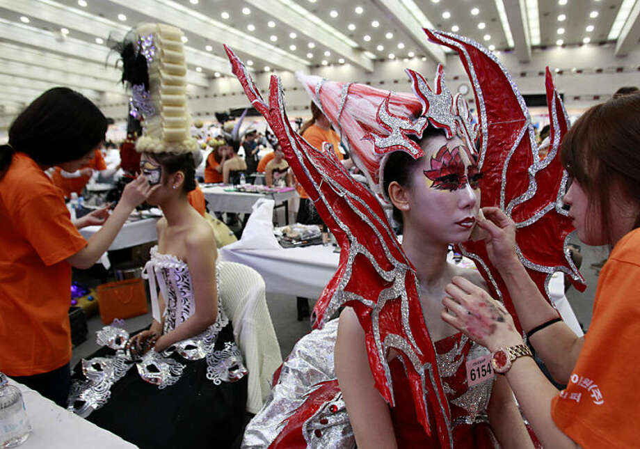 Models get their makeup done during K-Beauty World Fashion Festival in Gwacheon, South Korea, Tuesday, April 15, 2014. About 15,000 makeup artists, hairdressers, fashion designers and aestheticians from 56 countries participated in the annual event to promote the Korea culture. (AP Photo/Ahn Young-joon)