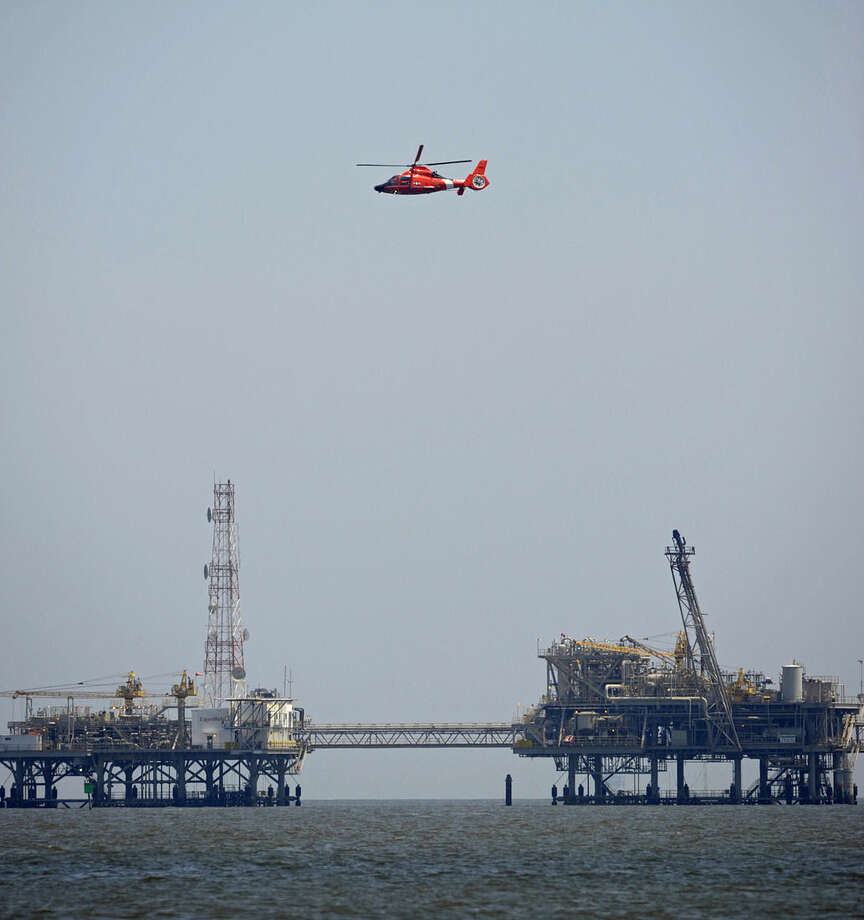 A U.S. Coast Guard helicopter flies over natural gas rigs in the waters of Mobile Bay off Dauphin Island, Ala., Sunday, April 26, 2015. Coast Guard crews are searching for five people missing in the water after a powerful storm capsized several sailboats participating in a regatta near Mobile Bay. (AP Photo/G.M. Andrews)