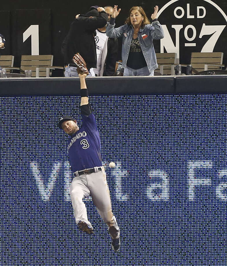 Colorado Rockies right fielder Michael Cuddyer can't make the catch on a deep drive by San Diego Padres' Alexi Amarista in the fifth inning of a baseball game Monday, April 14, 2014, in San Diego. Cuddyer could not make the catch and Amarista got a triple on the play. (AP Photo/Lenny Ignelzi)