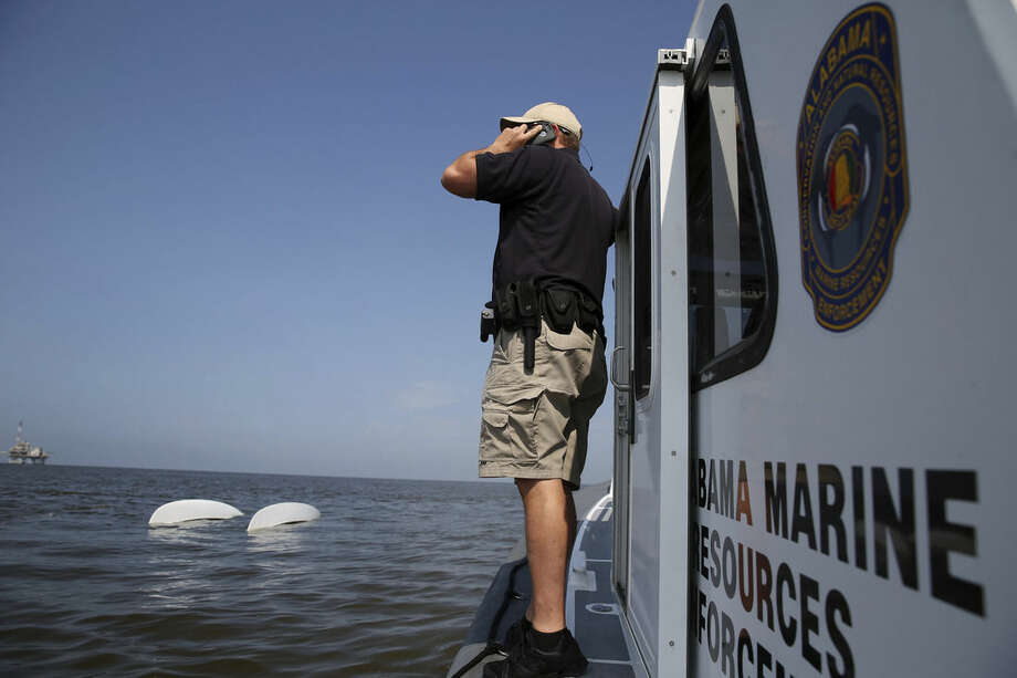 Lt. Jason Downey, of the Alabama Department of Conservation and Natural Resources, calls in a capsized catamaran as search and rescue operations continue off Dauphin Island, Ala. on Sunday, April 26, 2015. Coast Guard crews continued searching Sunday for five people missing in the water after recovering two bodies following a powerful storm that capsized several sailboats participating in a regatta near Mobile Bay, Ala. (Sharon Steinmann/AL.com via AP) MAGS OUT; MANDATORY CREDIT