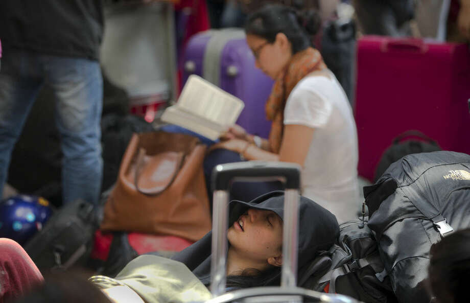 Foreign tourist and climbers wait for their flights at the Nepal International airport in Kathmandu, Nepal, Monday, April 27, 2015. A strong magnitude earthquake shook Nepal's capital and the densely populated Kathmandu valley on Saturday devastating the region and leaving tens of thousands shell-shocked and sleeping in streets. (AP Photo/Manish Swarup)