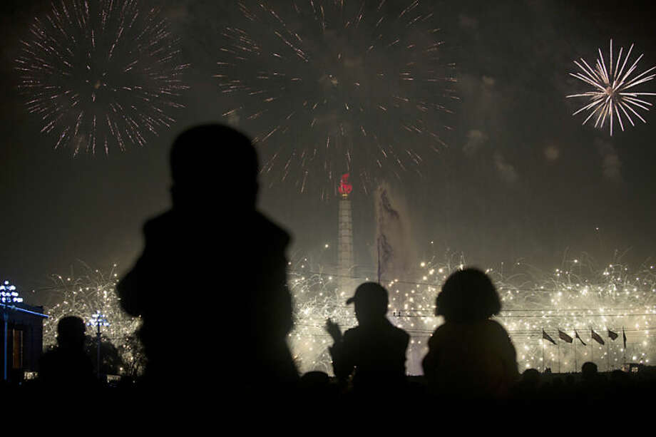 North Korean children sit on the shoulders of their parents at Kim Il Sung Square in Pyongyang to watch fireworks over Juche Tower to celebrate the official birthday of the late leader Kim Il Sung on Tuesday, April 15, 2014. (AP Photo/David Guttenfelder)