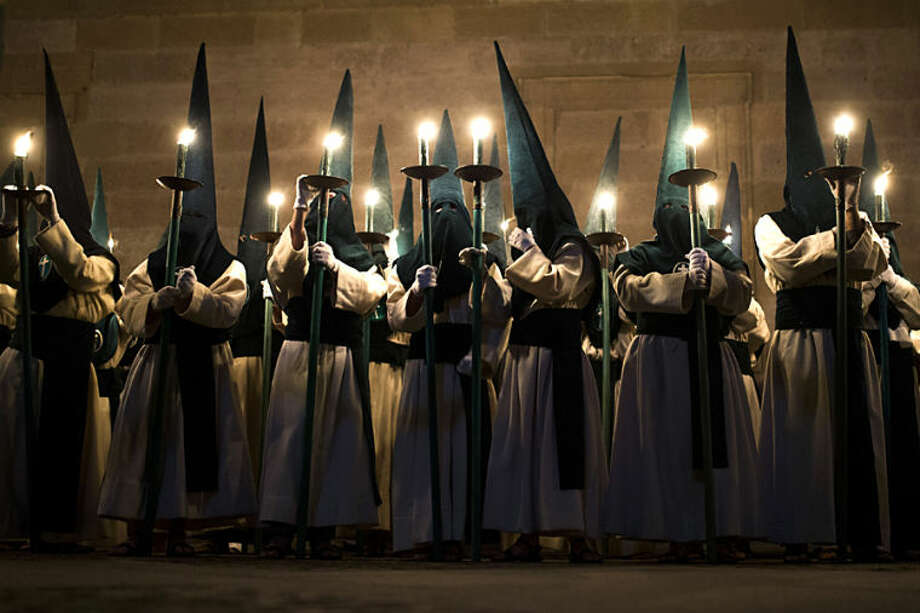 Penitents from 'Las Siete Palabras' 'Seven words' brotherhood take part in a procession in Zamora, Spain, on the early hours of Wednesday, April 16, 2014. Hundreds of processions take place throughout Spain during the Easter Holy Week. (AP Photo/Andres Kudacki)
