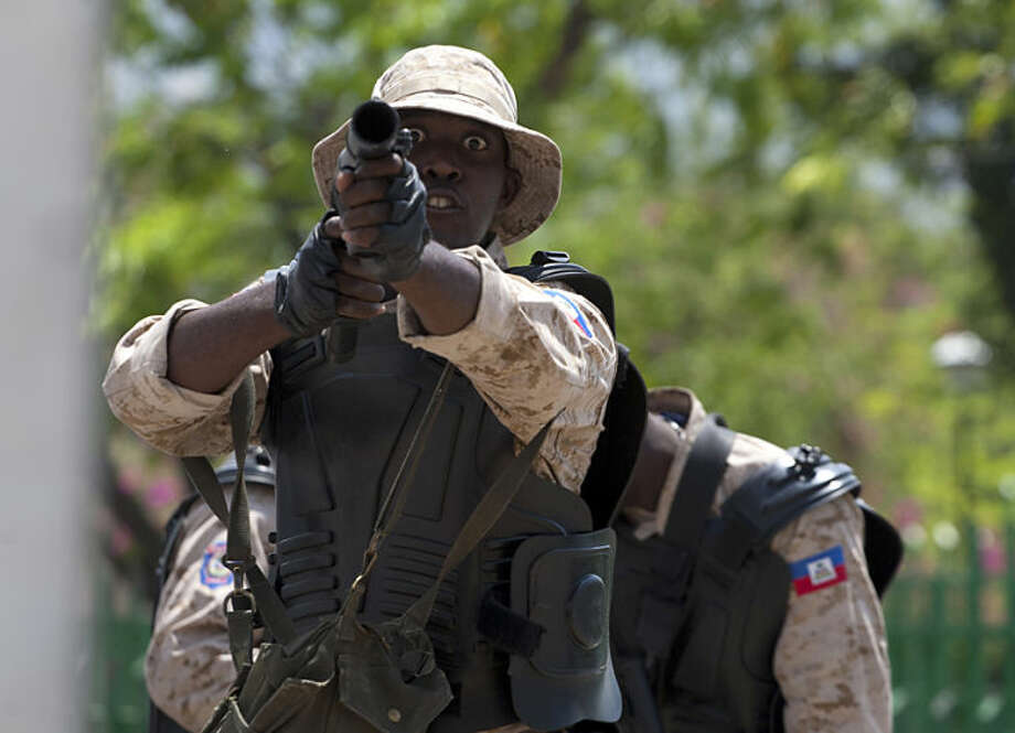 A National Police officer readies to fire tear gas at protestors during an anti-goverment protest in Port-au-Prince, Haiti, Tuesday April 15, 2014. The protesters called for the resignation of President Michel Martelly. ( AP Photo/Dieu Nalio Chery)