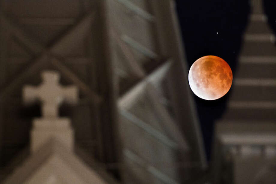 The moon glows a red hue during a lunar eclipse as it is framed between the steeples on the Annunciation Catholic Church in Houston, Tuesday, April 15, 2014. Tuesday's eclipse is the first of four total lunar eclipses that will take place between 2014 to 2015. (AP Photo/Houston Chronicle, Johnny Hanson)