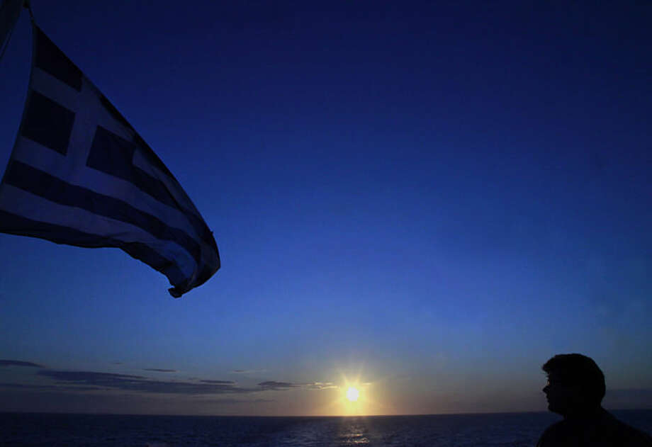 A man looks at the Greek flag aboard of the ferry Blue Star Paros during a sunset at the Aegean Sea on Tuesday, April 15, 2014. (AP Photo/Dimitri Messinis)