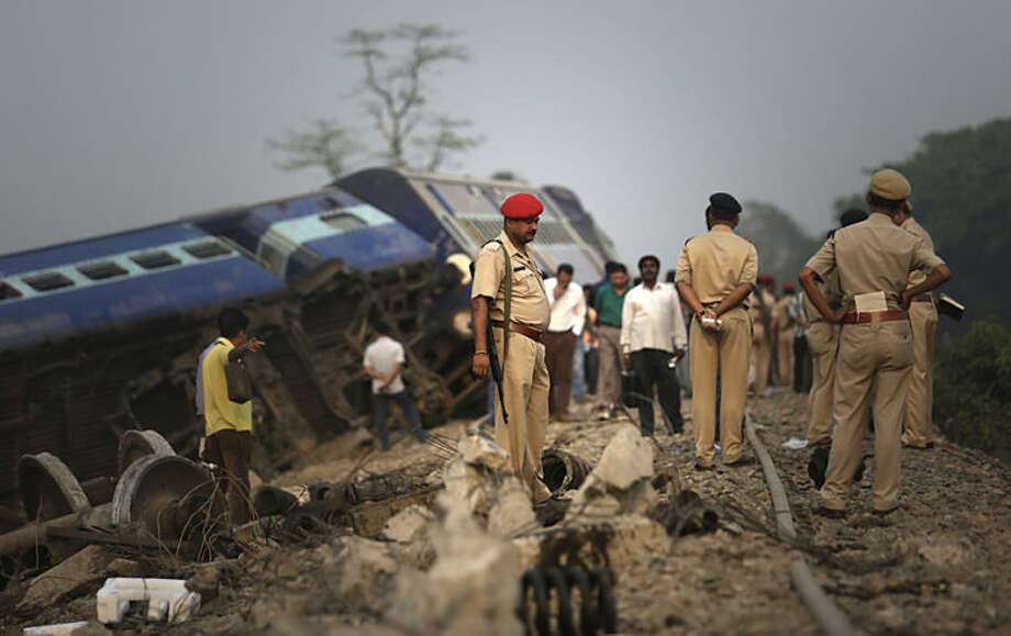 Indian policemen stand by a train that derailed near Jagiroad Railway Station, about 90 kilometers (56 miles) east of Gauhati, India, Wednesday, April 16, 2014. According to a Northeast Frontier Railway officer, dozens of people were injured when the train jumped the tracks and derailed early Wednesday. (AP Photo/Anupam Nath)