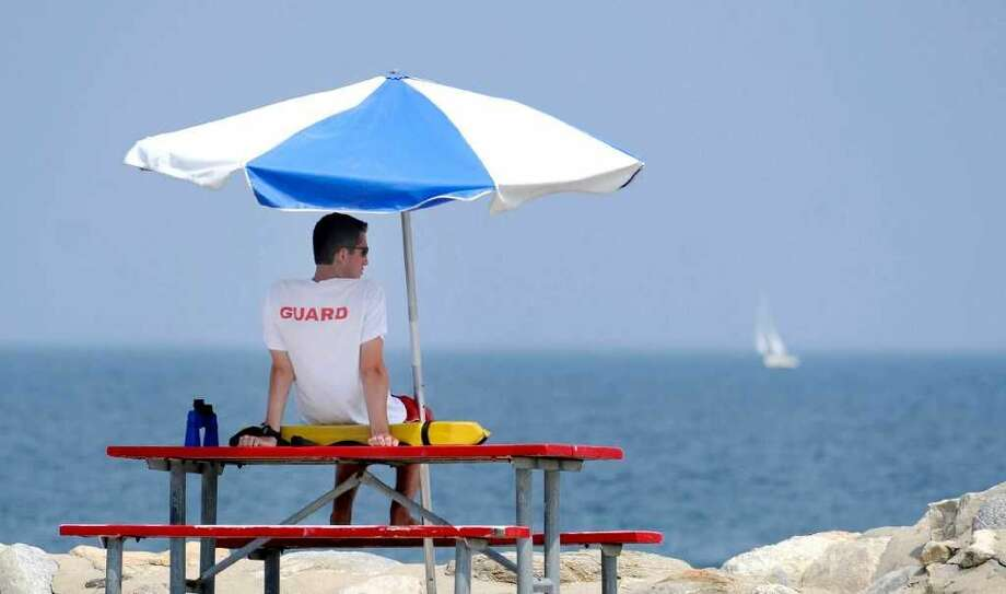 Greenwich Point Lifeguard Alex Coburn watches swimmers from underneath the protection of a blue and white umbrella at Greenwich Point, Thursday afternoon, July 21, 2011. (Photo: Bob Lucky)