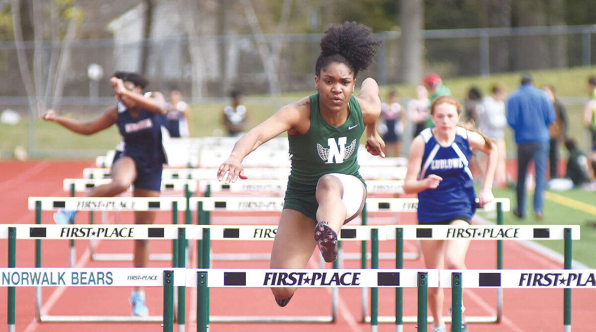 Hour photo/John Nash - Norwalk's Tamia Taylor, center, races to the win in the 100-meter hurdles during Monday's girls track meet against Brien McMahon and Fairfield Ludlowe.