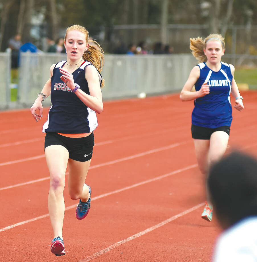 Hour photo/John Nash - Brien McMahon's Kristin Burnham, left, out-kicks a Fairfield Ludlowe runner to the finish line to win the 1,600-meter run at Monday's girls track meet at Testa Field at Norwalk High.