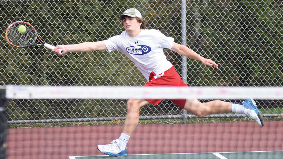 Hour photo/John Nash - Brien McMahon's Zach Ely extends for a return during his No. 1 singles match against Norwalk on Monday.