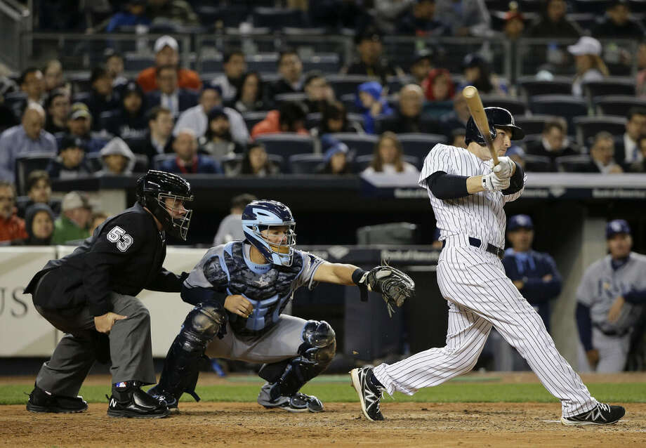 New York Yankees second baseman Stephen Drew (14) follows through on a double to right field that scored Carlos Beltran against the Tampa Bay Rays in the sixth inning of a baseball game, Monday, April 27, 2015, in New York. (AP Photo/Julie Jacobson)