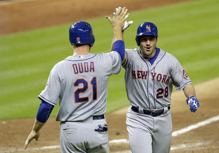 New York Mets' Daniel Murphy (28) is congratulated by teammate Lucas Duda (21), who scored after Murphy hit a three-run home run against the Miami Marlins in the ninth inning of a baseball game, Monday, April 27, 2015, in Miami. Juan Lagares also scored on the home run. The Mets won 3-1. (AP Photo/Alan Diaz)