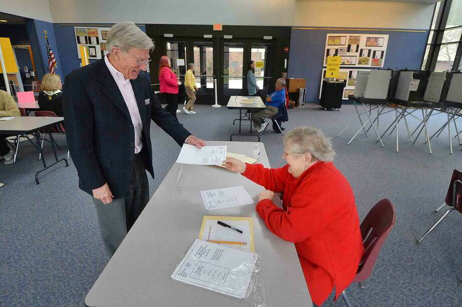 Roger Valkenberg gets a ballot from Ballot Clerk Ann Klotz during Wilton High School District 1 during Presidential Primary voting in Wilton Conn. on Tuesday April 26