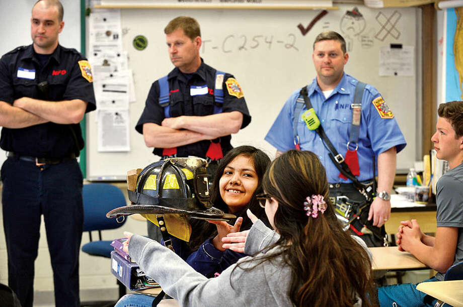 Hour photo / Erik Trautmann Students Castillo Cardoso and Yoliana Saborion look over a Norwalk firefighters helmet during the Annual 8th Grade Career Day Friday at West Rocks Middle School.