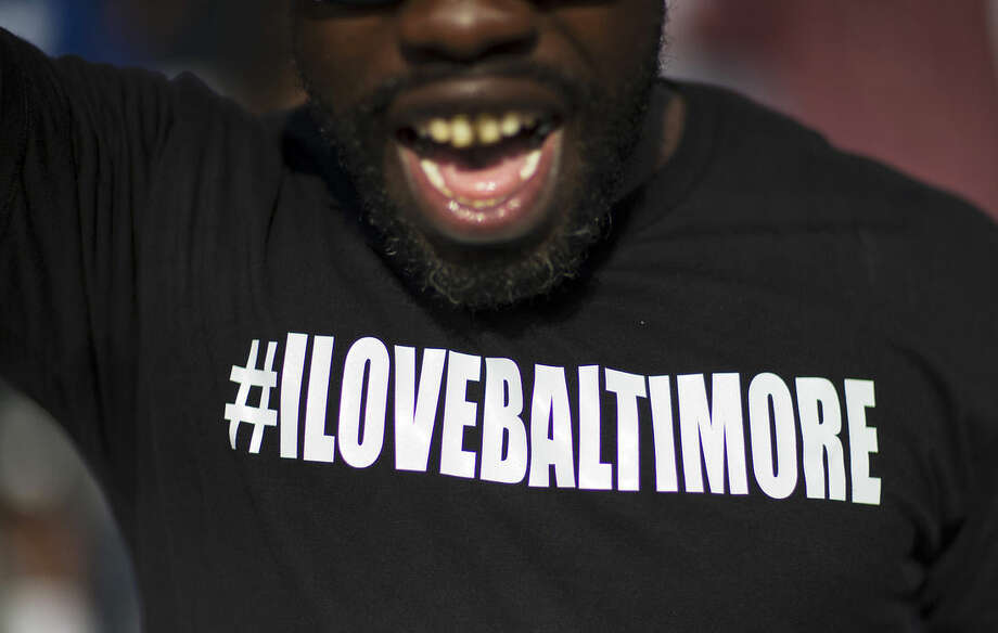 """A message reading """"I Love Baltimore"""" is written across a T-Shirt worn by Rashid Scott as he marches with protesters toward City Hall to demonstrate the police-custody death of Freddie Gray, Thursday, April 30, 2015, in Baltimore. (AP Photo/David Goldman)"""