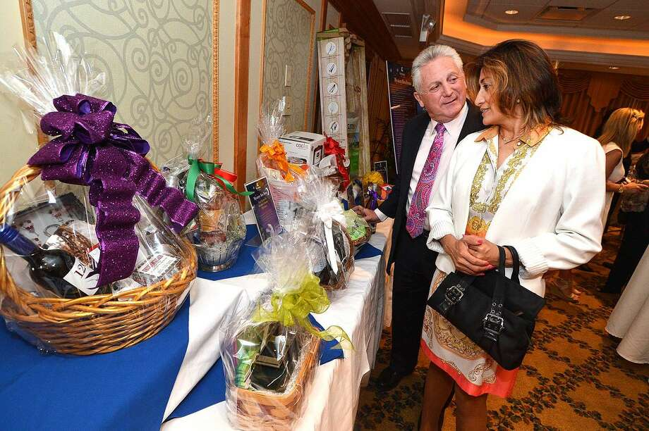 Hour Photo/Alex von Kleydorff Mayor Harry Rilling and wife Lucia bid on an item at the silent auction at the Mystery gala to benefit Keystone House