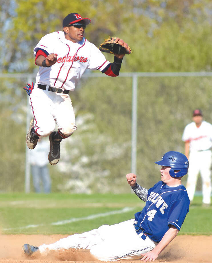 Brien McMahon's Edwin Owolo jumps up as a Fairfield Ludlowe runner slides into second base. (John Nash/Hour photo