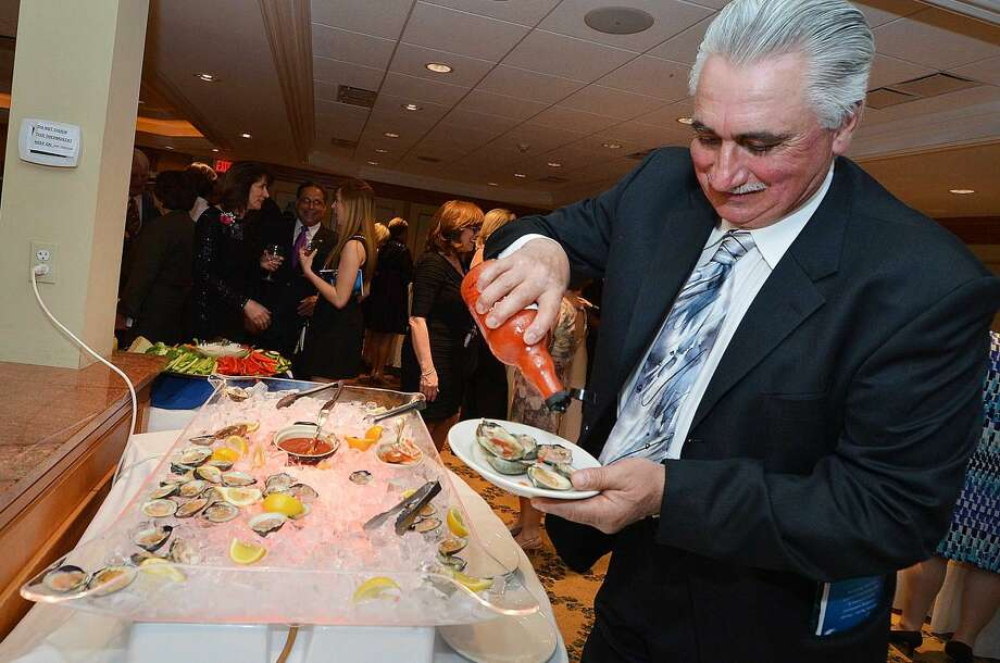 Hour Photo/Alex von Kleydorff Neil Buona pours on the hot sauce for his oysters from the raw bar during the Mystery gala to benefit Keystone House