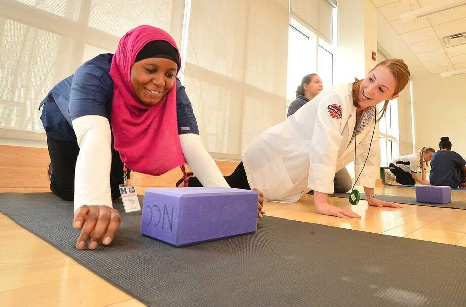 Hour Photo/Alex von Kleydorff Brien McMahon student Diana Muteba does some push ups with NCC faculty Instructor Nicole Hafner to measure stength during NCC's Medical Academy