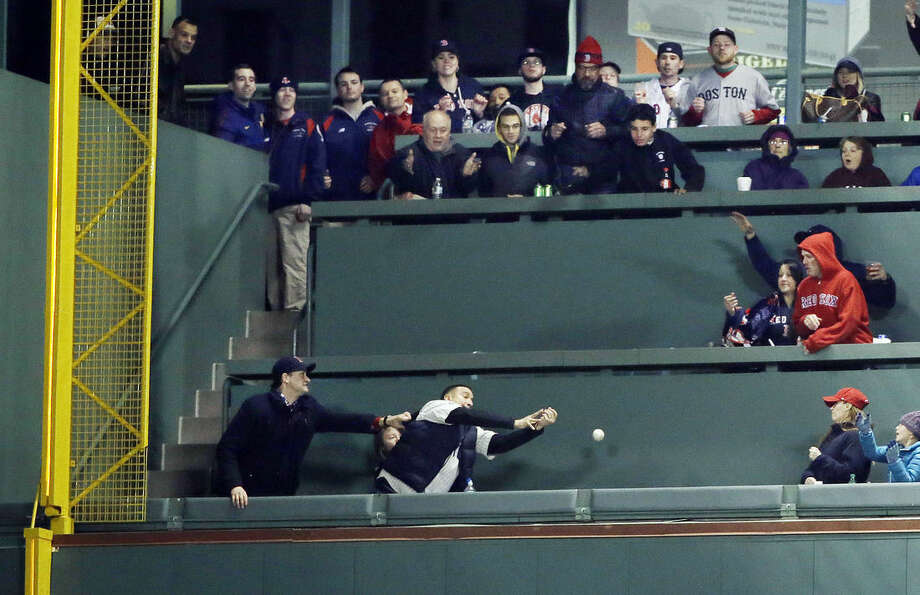 A fan in the Green Monster seats tries to catch a solo homer to left by Boston Red Sox's Allen Craig in the fourth inning of a baseball game at Fenway Park in Boston, Friday, May 1, 2015. (AP Photo/Elise Amendola)