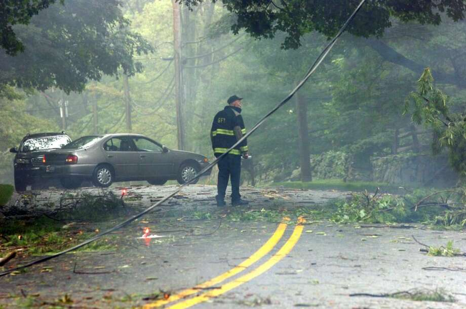 071206-Round Hill Road--Greenwich--Former Round Hill Fire Department Chief Bill Strain redirects the flow of traffic after a tornado downed power lines and trees. The damage stretched across the backcountry of Greenwich from Riversville to the Parkway, Strain said. Keelin Daly/ Staff Photo