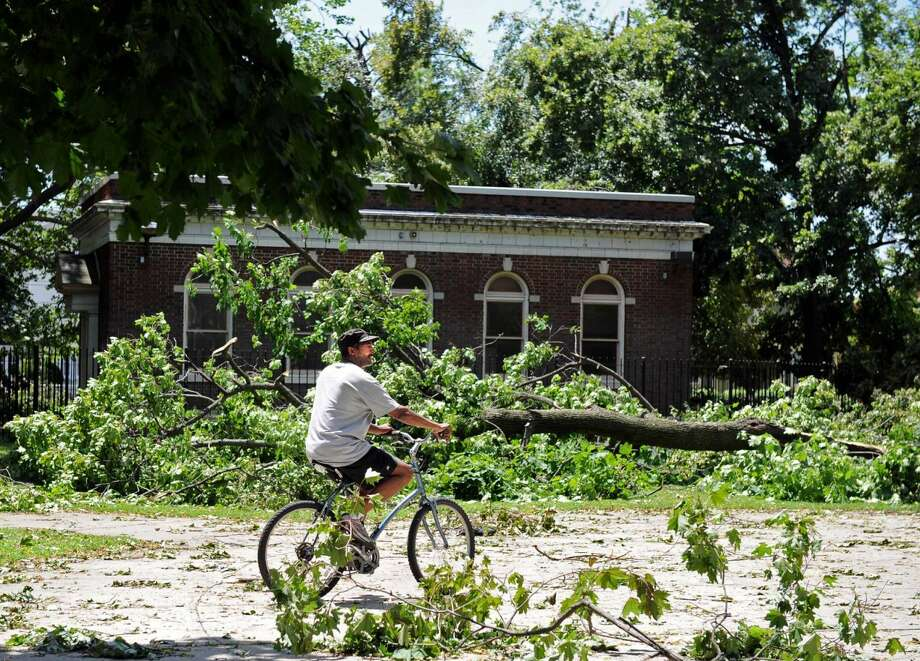 Tony Williamson, of Bridgeport, rides his bike past downed trees at Washington Park in Bridgeport Friday June 25, 2010. The damage was the result of a tornado with 100 mph winds that touched down in Bridgeport Thursday.