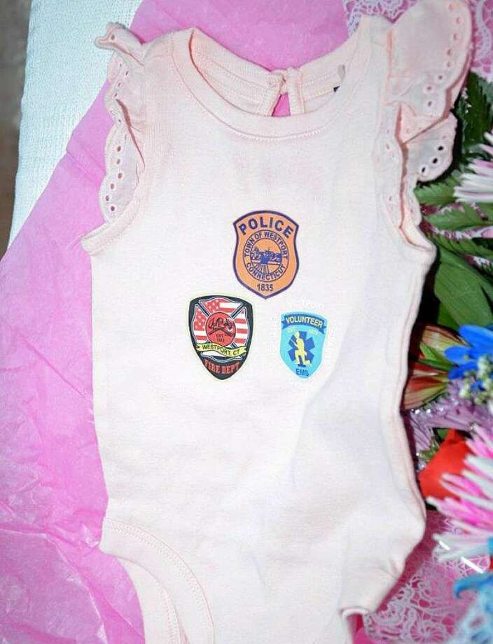 Speical baby clothes -- featuring emblems of Westport emergency services that helped deliver Mila Joy Procaccini at home when her mother went into early labor -- were given to parents Kate and John Procacinni by representatives of the police, firefighters and paramedics at the scene. (Photo: Westport Police)