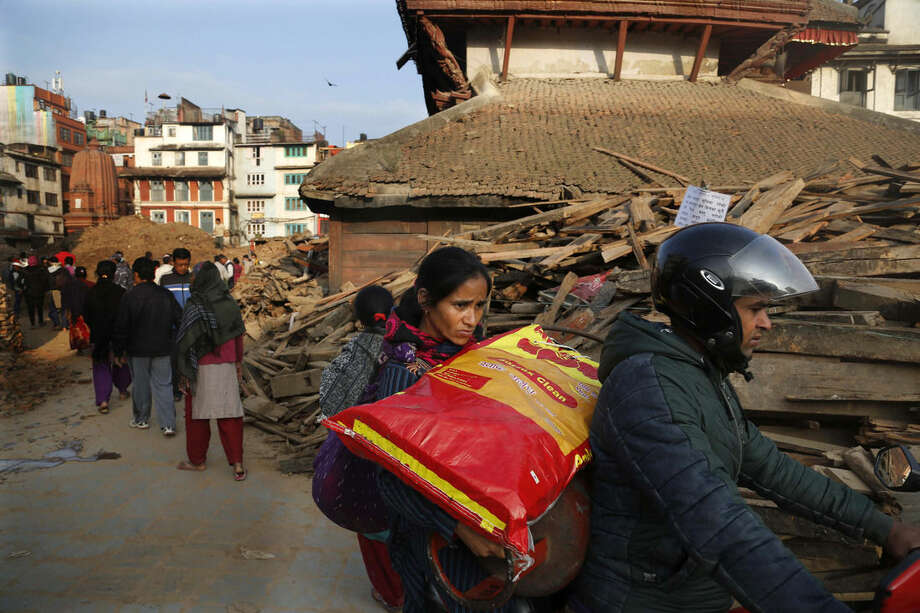 A Nepalese couple rides past while carrying a sack of wheat flour through earthquake damaged buildings in Kathmandu, Nepal, Friday, May 1, 2015. A strong magnitude earthquake shook Nepal on Saturday devastating the region and leaving some thousands shell-shocked and displaced. (AP Photo/Manish Swarup)