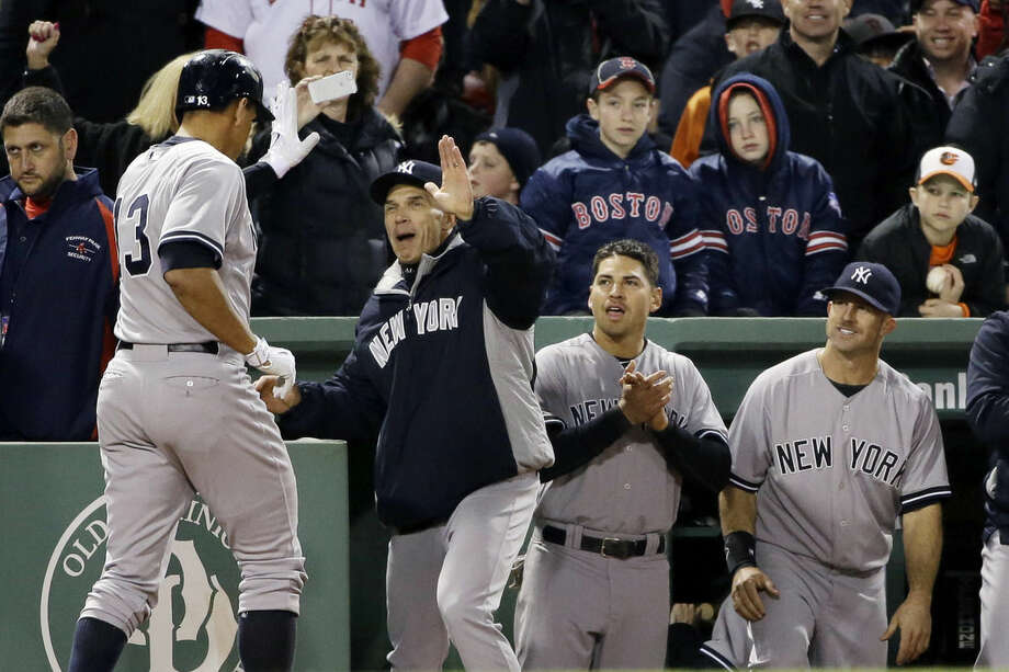 New York Yankees pinch hitter Alex Rodriguez is congratulated by manager Joe Girardi at the dugout after hitting a solo homer in the eighth inning of a baseball game against the Boston Red Sox at Fenway Park in Boston, Friday, May 1, 2015. Rodriguez has now tied slugger Willie Mays with 660 career home runs. (AP Photo/Elise Amendola)