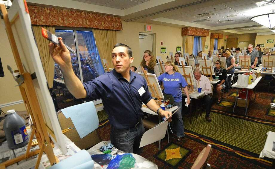 Hour Photo/Alex von Kleydorff Professional artist Eddie Niño gives the crowd some tips for their paintings with an Earth day theme at Arts and Carafes at The Hilton Garden Inn on Friday.